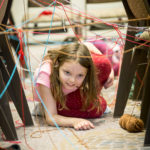 Child crawling through a yarn laser maze