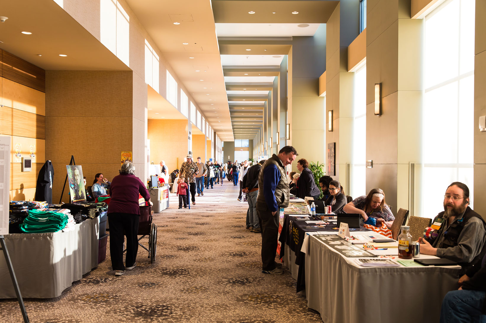 Picture of the hallway outside of dealers with people talking and walking