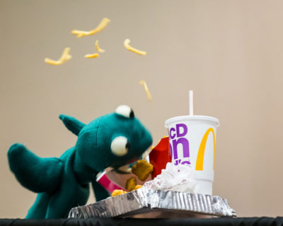 Puppet demolishing a fast food meal with fries flying