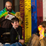 David Abzug and son sitting in front of a campfire on stage at Capricon 36 opening ceremonies